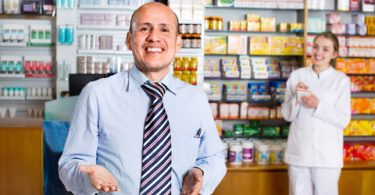Smiling pleasant glad pharmacist and pharmacy technician posing in drugstore