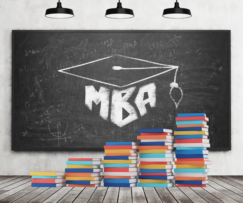 A stair is made of colourful books. A graduation hat is drawn on the black chalkboard. MBA concept. Concrete wall, wooden floor and three black ceiling lights.