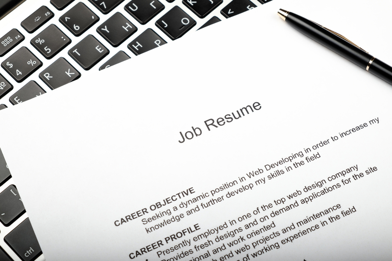 Resume and black pen on laptop in a home office