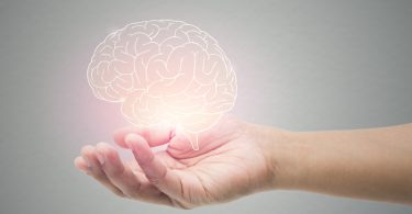Man holding brain illustration against gray wall background.