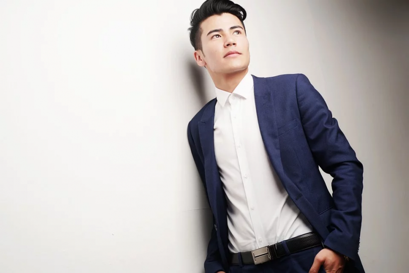 young male entrepreneur in suit leaning up against white wall