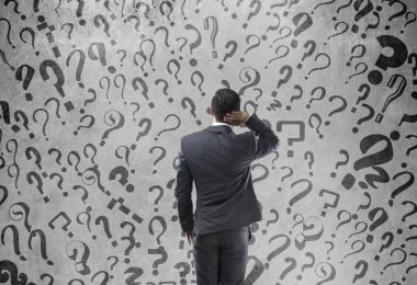 Rear view of confused Indian businessman with question marks on wall
