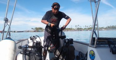 marine biologist preparing his scuba gear to make a dive