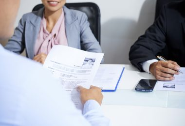 applicant holding resume in hands while being interviewed by employers