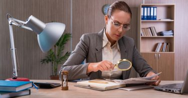 female forensic accountant studying documents with a magnifying glass