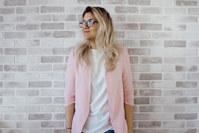 blode female wearing pink shirt standing in front of brick wall smiling