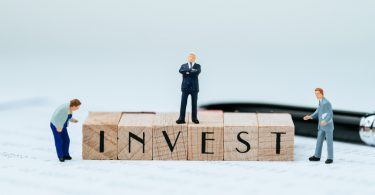 small businessmen figures looking at the word invest printed on building blocks