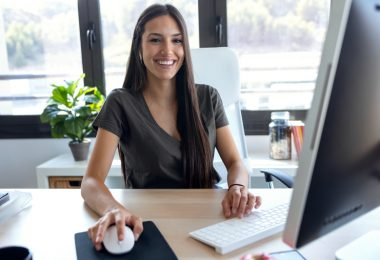 smiling woman working on computer in office