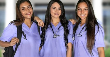 three young smiling female nurses wearing purple scrubs