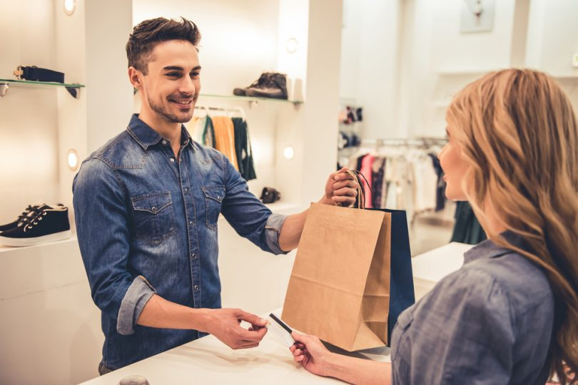 shop assistant is smiling while giving purchases and credit card to customer